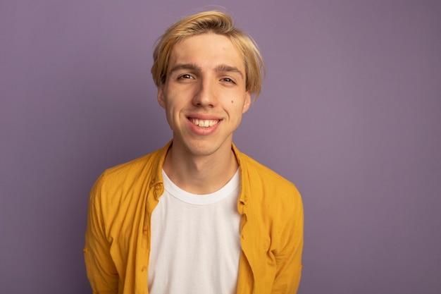 Uśmiechnięty młody blondyn na sobie żółtą koszulkę, trzymając się za ręce w talii