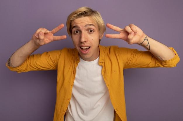 Uśmiechnięty młody blondyn patrząc prosto przed siebie na sobie żółtą koszulkę przedstawiającą gest pokoju na fioletowym tle