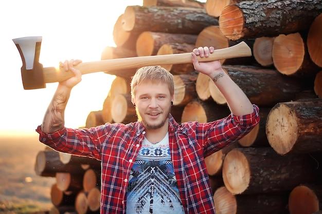 Uśmiechnięty młody brodaty drwal niosący siekierę i stojąc na tle drewna