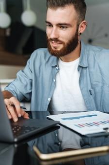 Uśmiechnięty młody brodaty mężczyzna pracuje na laptopie, siedząc przy kuchennym stole i analizując dokumenty
