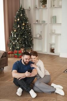 Uśmiechnięty młody brodaty mężczyzna siedzi na podłodze w salonie z choinką i pokazuje wideo na p...