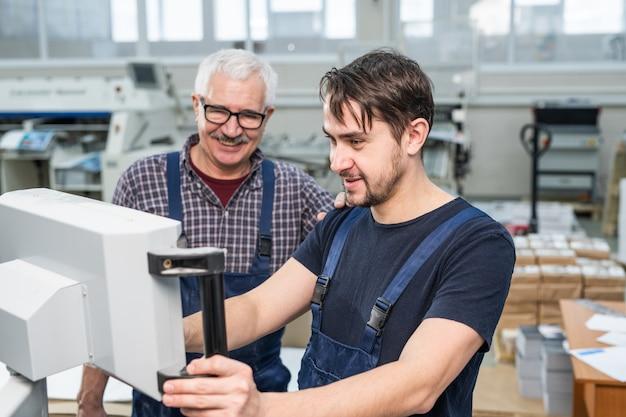 Uśmiechnięty młody brodaty stażysta w drukarni obsługującej maszynę pod kontrolą doświadczonego specjalisty w warsztacie