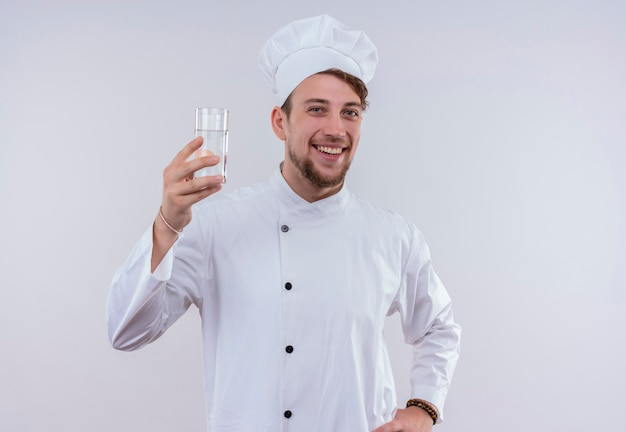 Uśmiechnięty młody brodaty szef kuchni ubrany w biały mundur kuchenki i kapelusz pokazujący szklankę wody, patrząc na białej ścianie
