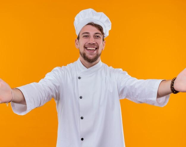 Uśmiechnięty młody brodaty szef kuchni w białym mundurze, otwierając szeroko ramiona do uścisku, patrząc na pomarańczową ścianę