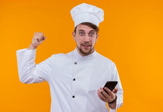 Uśmiechnięty młody brodaty szef kuchni w białym mundurze, trzymając telefon komórkowy, patrząc z zaciśniętą pięścią na pomarańczowej ścianie
