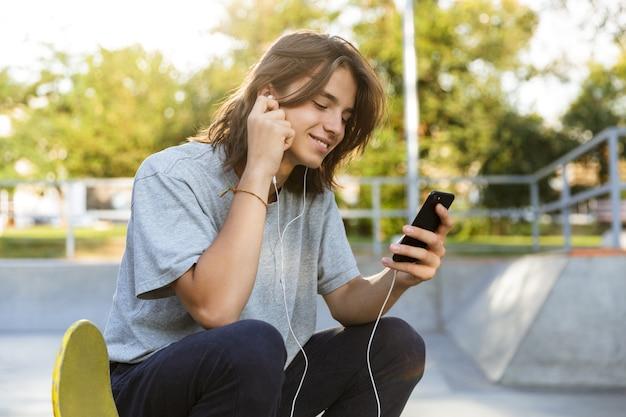 Uśmiechnięty młody chłopak spędza czas w skate parku, słuchając muzyki przez słuchawki