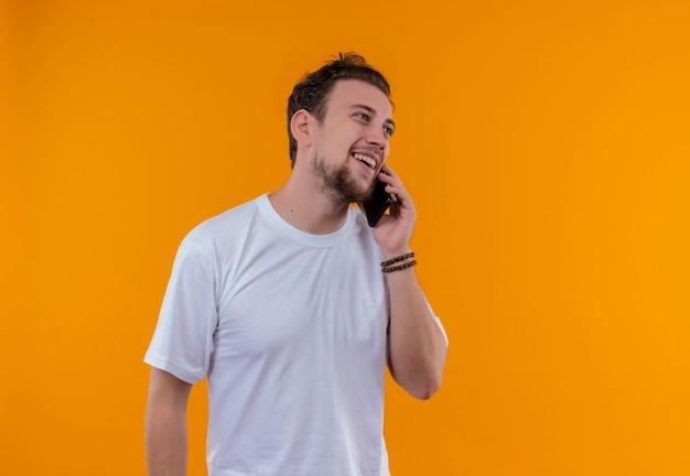 Uśmiechnięty młody chłopak ubrany w białą koszulkę mówi przez telefon na na białym tle pomarańczowym tle