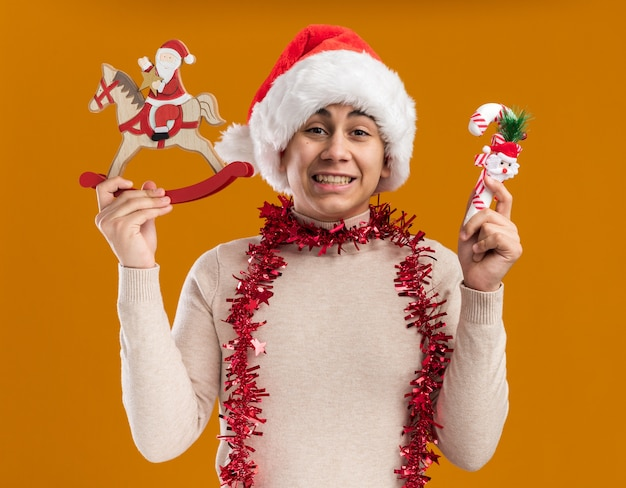 Uśmiechnięty młody chłopak ubrany w świąteczny kapelusz z girlandą na szyi trzyma świąteczną zabawkę z cukierkami na białym tle na żółtym tle