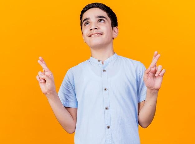 Uśmiechnięty młody chłopiec kaukaski patrząc skrzyżowanymi palcami, którzy chcą szczęścia na białym tle na pomarańczowym tle