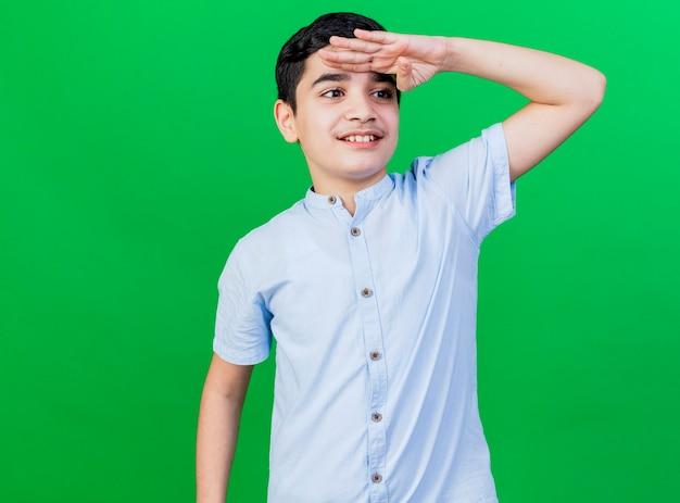 Uśmiechnięty młody chłopiec kaukaski patrząc z boku na odległość na białym tle na zielonej ścianie z miejsca na kopię