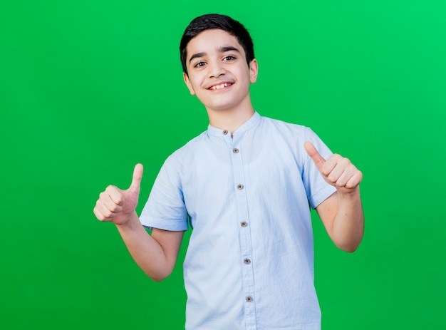 Uśmiechnięty młody chłopiec kaukaski pokazując kciuki do góry na białym tle na zielonej ścianie
