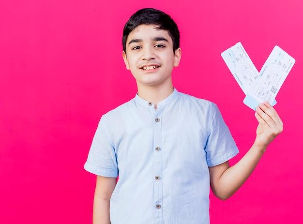 Uśmiechnięty młody chłopiec kaukaski trzymając bilety lotnicze patrząc na kamery na białym tle na szkarłatnym tle z miejsca na kopię