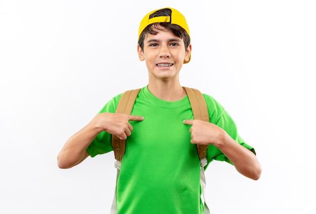 Uśmiechnięty młody chłopiec w szkole noszący plecak z czapką wskazuje na siebie na białym tle na białej ścianie