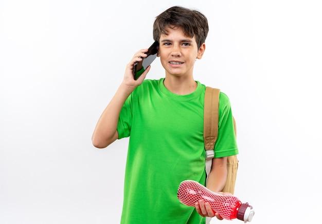 Uśmiechnięty młody chłopiec w szkole w plecaku trzymającym butelkę z wodą rozmawia przez telefon na białym tle na białej ścianie z miejscem na kopię