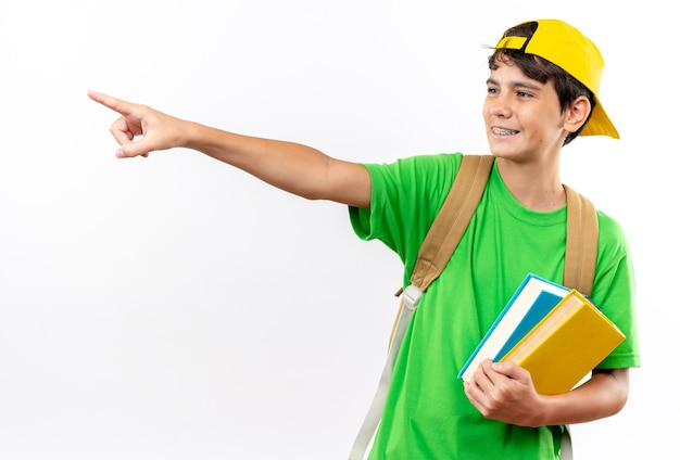 Uśmiechnięty młody chłopiec w szkole w plecaku z czapką trzymający książki wskazuje z boku