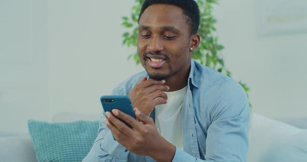 Uśmiechnięty młody człowiek afryki siedzi na wygodnej kanapie i przy użyciu smartfona