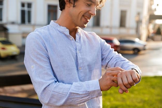 Uśmiechnięty młody człowiek dorywczo dostosowując swój inteligentny zegarek
