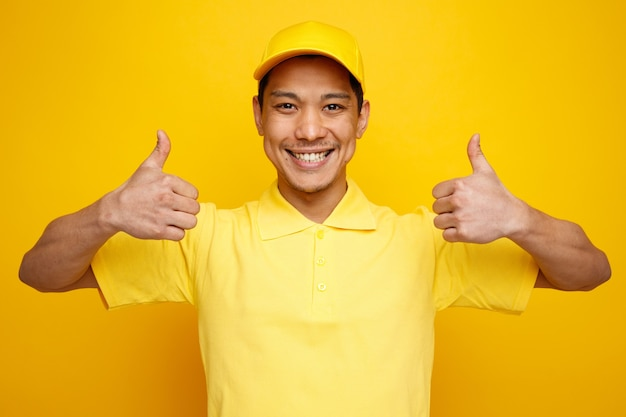 Uśmiechnięty młody człowiek dostawy czapka i mundur pokazuje kciuki do góry