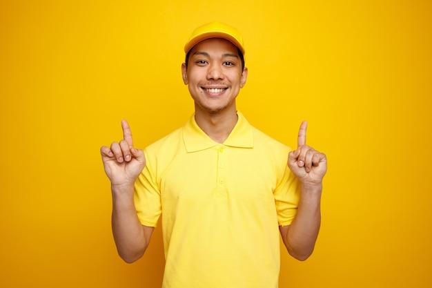 Uśmiechnięty młody człowiek dostawy czapkę i mundur skierowaną ku górze