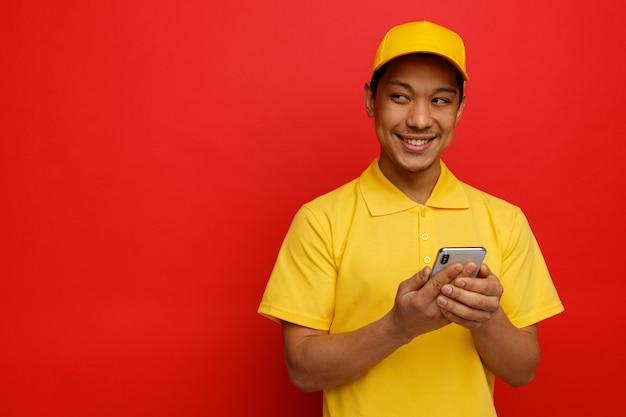 Uśmiechnięty młody człowiek dostawy czapkę i mundur trzymając telefon komórkowy patrząc na bok