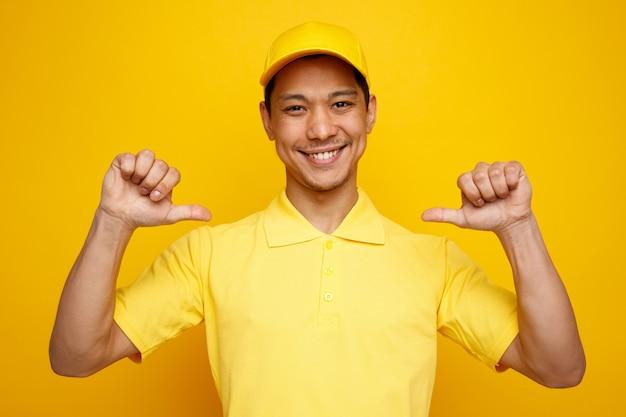Uśmiechnięty młody człowiek dostawy czapkę i mundur, wskazując na siebie