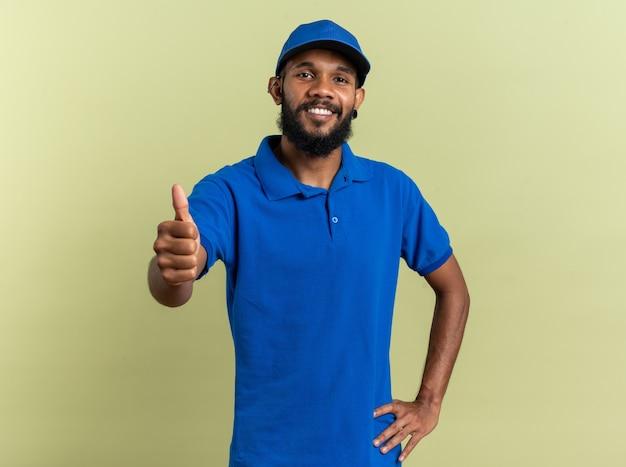 Uśmiechnięty młody człowiek dostawy kciukiem na białym tle na oliwkowozielonej ścianie z miejscem na kopię