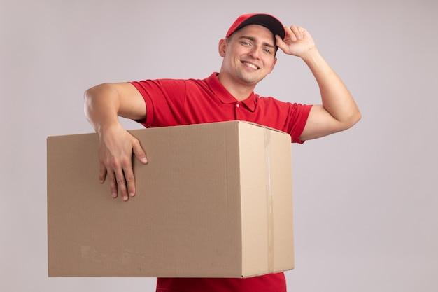 Uśmiechnięty młody człowiek dostawy na sobie mundur z czapką, trzymając duże pudełko i czapkę na białym tle na białej ścianie