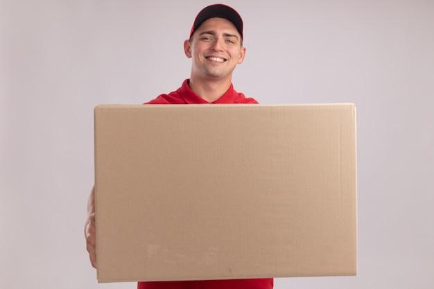Uśmiechnięty młody człowiek dostawy na sobie mundur z czapką, trzymając duże pudełko na białym tle na białej ścianie