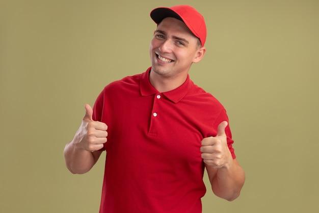 Uśmiechnięty młody człowiek dostawy ubrany w mundur i czapkę pokazując kciuki do góry na białym tle na oliwkowej ścianie