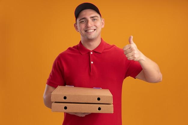 Uśmiechnięty młody człowiek dostawy ubrany w mundur z czapką trzyma pudełka po pizzy pokazując kciuk do góry na białym tle na pomarańczowej ścianie
