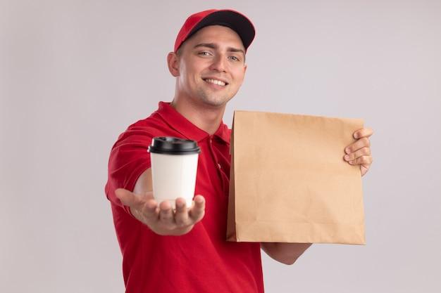Uśmiechnięty młody człowiek dostawy ubrany w mundur z czapką, trzymając papierowy pakiet żywności i trzymając filiżankę kawy z przodu na białym tle na białej ścianie