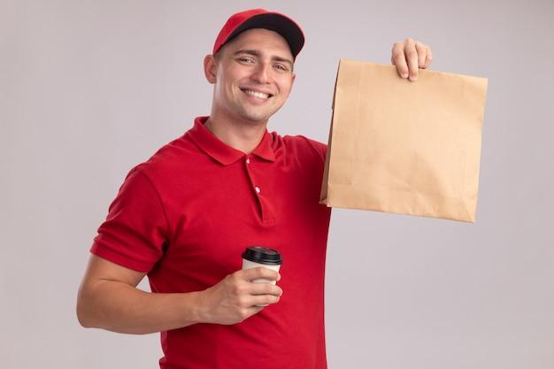 Uśmiechnięty młody człowiek dostawy ubrany w mundur z czapką trzymając papierowy pakiet żywności z filiżanką kawy na białym tle na białej ścianie
