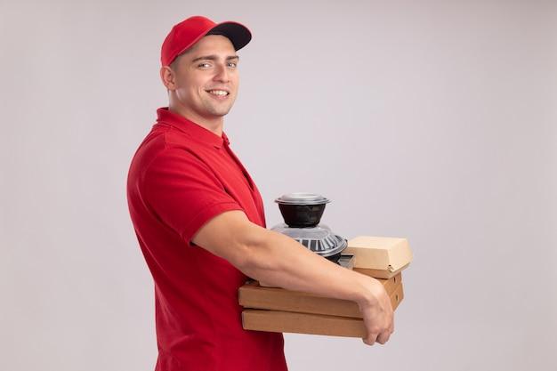 Uśmiechnięty młody człowiek dostawy ubrany w mundur z czapką, trzymając pojemniki na żywność na pudełkach po pizzy na białym tle na białej ścianie