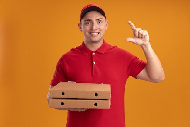 Uśmiechnięty młody człowiek dostawy ubrany w mundur z czapką, trzymając pudełka po pizzy pokazujące rozmiar na białym tle na pomarańczowej ścianie