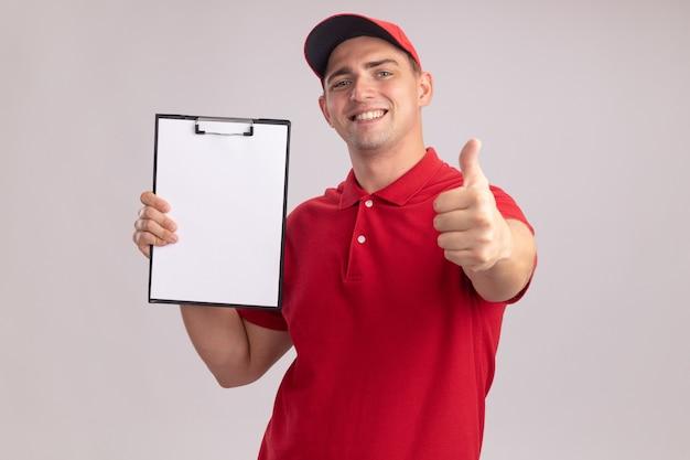 Uśmiechnięty młody człowiek dostawy ubrany w mundur z czapką trzymając schowek pokazując kciuk do góry na białym tle na białej ścianie