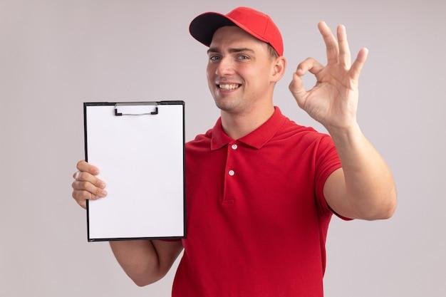 Uśmiechnięty młody człowiek dostawy ubrany w mundur z czapką trzymającą schowek pokazujący dobry gest na białej ścianie