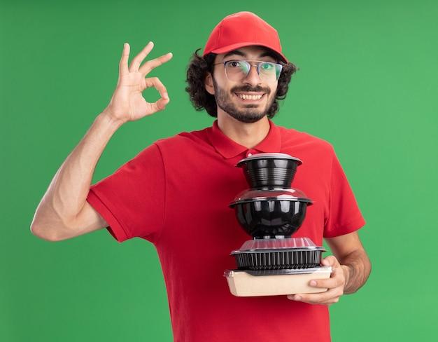 Uśmiechnięty młody człowiek dostawy w czerwonym mundurze i czapce w okularach, trzymając papierowe opakowanie żywności i pojemniki na żywność, patrząc na przód robi ok znak na zielonej ścianie