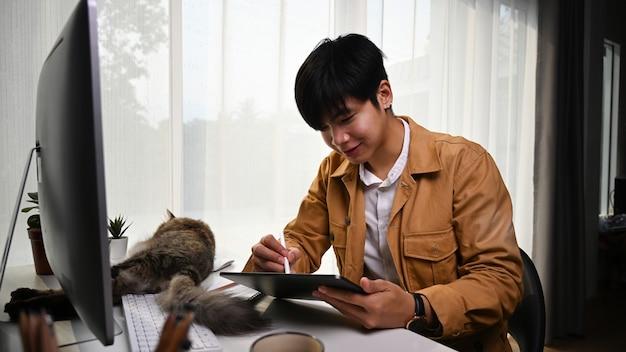 Uśmiechnięty młody człowiek grafik pracujący online z cyfrowym tabletem i jego kotem leżącym przed nim.