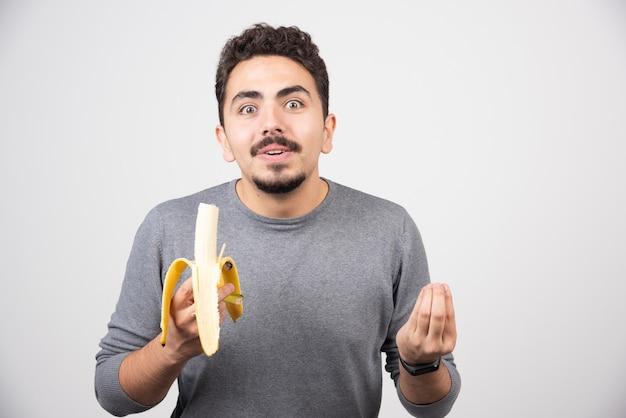 Uśmiechnięty młody człowiek je banana na białej ścianie.