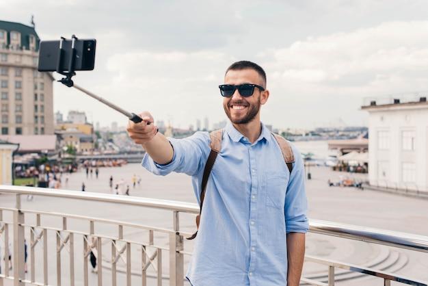 Uśmiechnięty młody człowiek jest ubranym okulary przeciwsłonecznych bierze selfie z smartphone