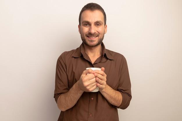 Uśmiechnięty młody człowiek kaukaski trzymając filiżankę herbaty patrząc na kamery na białym tle na białym tle z miejsca kopiowania