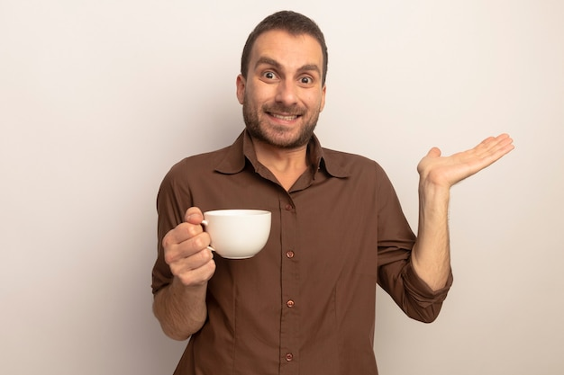 Uśmiechnięty młody człowiek kaukaski trzymając filiżankę herbaty patrząc na kamery pokazując pustą rękę na białym tle na białym tle z miejsca kopiowania