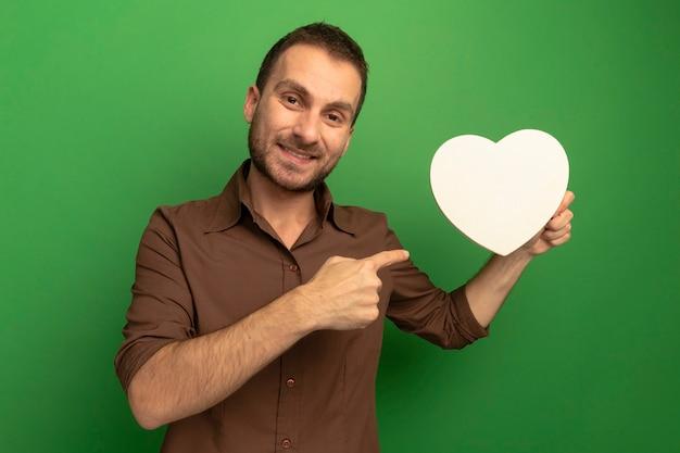 Uśmiechnięty młody człowiek kaukaski trzymając i wskazując na kształt serca patrząc na kamery na białym tle na zielonym tle