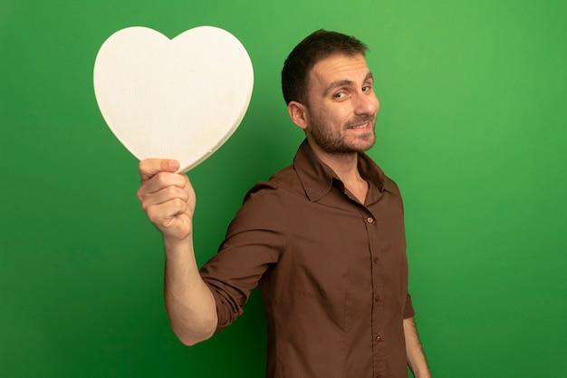 Uśmiechnięty młody człowiek kaukaski wyciągając kształt serca w kierunku kamery patrząc na kamery na białym tle na zielonym tle z miejsca na kopię