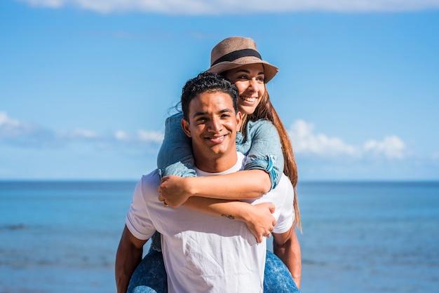 Uśmiechnięty młody człowiek niosący kobietę na plecach i śmiejąc się na zewnątrz - młoda para ludzi na barana bawić się razem z błękitnym oceanem i niebem