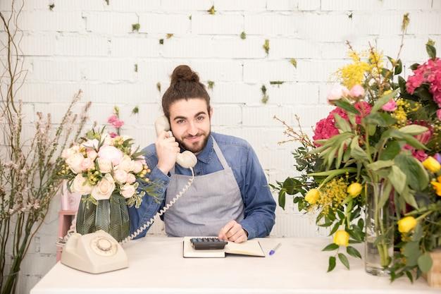 Uśmiechnięty młody człowiek opowiada na telefonicznym używa kalkulatorze w kwiaciarnia sklepie