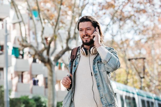 Uśmiechnięty młody człowiek opowiada na telefonie komórkowym przy outdoors z jego plecakiem