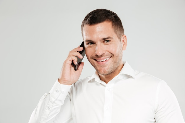Uśmiechnięty młody człowiek opowiada telefonem.