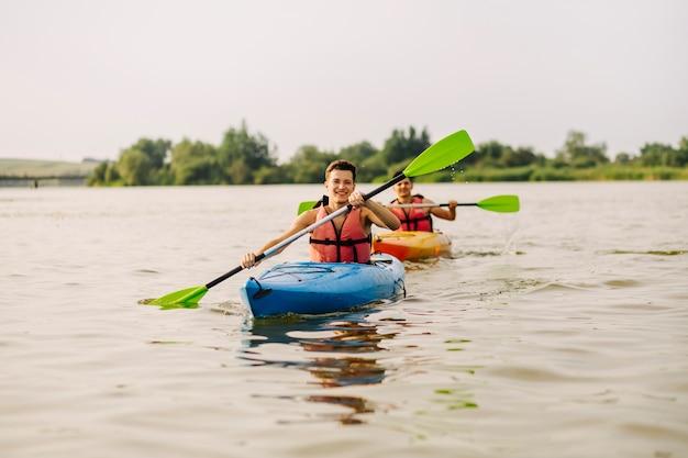 Uśmiechnięty młody człowiek paddling kajak z jego przyjacielem na jeziorze