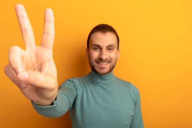 Uśmiechnięty młody człowiek patrząc na przód robi znak pokoju na białym tle na pomarańczowej ścianie